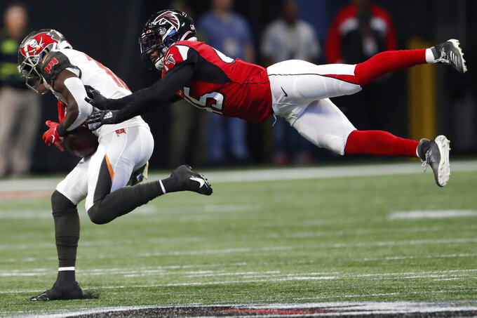 Atlanta Falcons linebacker Deion Jones (45) misses the tackle on Tampa Bay Buccaneers wide receiver Chris Godwin (12) during the first half of an NFL football game, Sunday, Nov. 24, 2019, in Atlanta. Godwin scored a touchdown. (AP Photo/John Bazemore)
