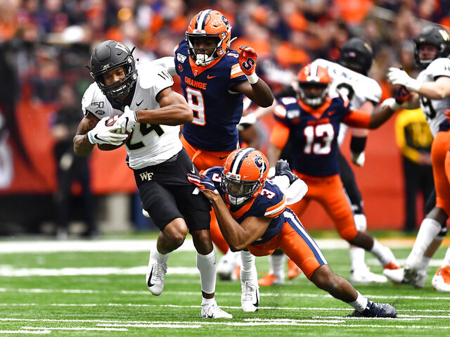 Wake Forest wide receiver Donavon Greene, left, is tackled by Syracuse defensive back Christopher Fredrick after a reception during the first half of an NCAA college football game in Syracuse, N.Y., Saturday, Nov. 30, 2019. (AP Photo/Adrian Kraus)