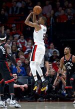Portland Trail Blazers guard Rodney Hood, center, shoots between Toronto Raptors forward Rondae Hollis-Jefferson, left, and guard Norman Powell, right, during the second half of an NBA basketball game in Portland, Ore., Wednesday, Nov. 13, 2019. (AP Photo/Craig Mitchelldyer)