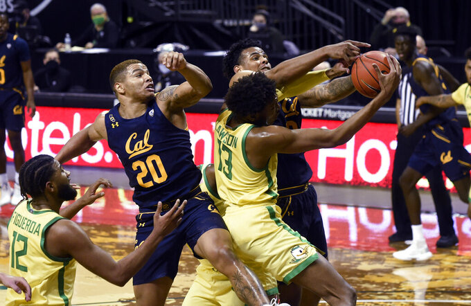 Oregon guard LJ Figuero (12), California guard Matt Bradley (20), Oregon orward Chandler Lawson (13) and Oregon center Franck Kepnang (22) vie for a rebound during the first half of an NCAA college basketball game in Eugene, Ore., Friday, Dec. 31, 2020. (AP Photo/Andy Nelson)