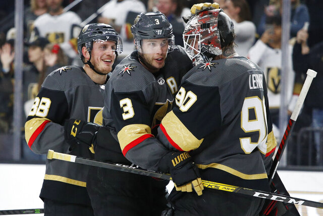 Vegas Golden Knights defenseman Nate Schmidt, left, defenseman Brayden McNabb (3) and Robin Lehner (90) celebrate after defeating the Buffalo Sabres in an NHL hockey game Friday, Feb. 28, 2020, in Las Vegas. (AP Photo/John Locher)
