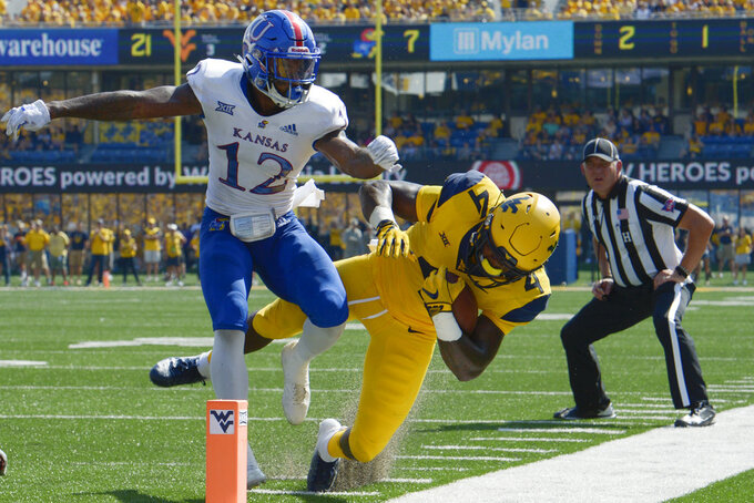 West Virginia running back Leddie Brown (4) is knocked out of bounds by Kansas safety Jeremiah McCullough (12) during an NCAA college football game against Kansas in Morgantown, W. Va., Saturday Oct. 6, 2018. (AP Photo/Craig Hudson)