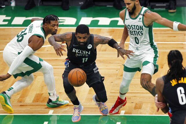 Brooklyn Nets' Kyrie Irving (11) loses control of the ball against Boston Celtics' Marcus Smart (36) and Jayson Tatum (0) during the first half of an NBA basketball game, Friday, Dec. 25, 2020, in Boston. (AP Photo/Michael Dwyer)