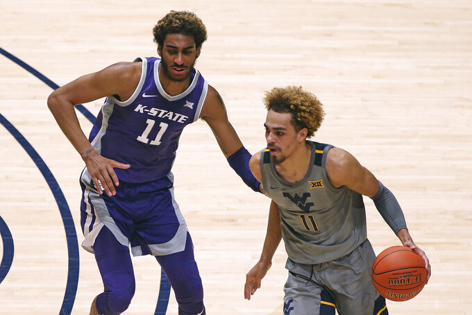 West Virginia forward Emmitt Matthews Jr. (11) is defended by Kansas State forward Antonio Gordon (11) during the first half of an NCAA college basketball game Saturday, Feb. 27, 2021, in Morgantown, W.Va. (AP Photo/Kathleen Batten)