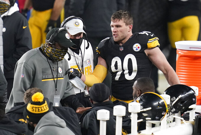 Pittsburgh Steelers head coach Mike Tomlin, left, talks with his defense, including outside linebacker T.J. Watt (90), during the second half of an NFL wild-card playoff football game against the Cleveland Browns, Sunday, Jan. 10, 2021, in Pittsburgh. (AP Photo/Keith Srakocic)