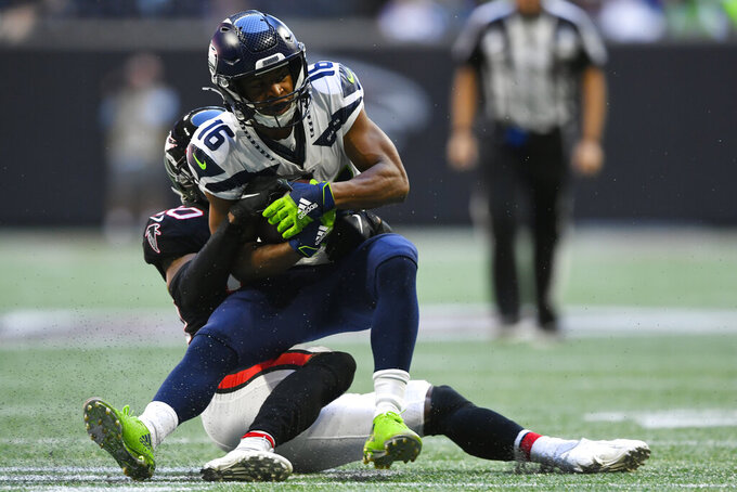 Atlanta Falcons defensive back Kendall Sheffield (20) hits Seattle Seahawks wide receiver Tyler Lockett (16) during the first half of an NFL football game, Sunday, Oct. 27, 2019, in Atlanta. (AP Photo/John Amis)