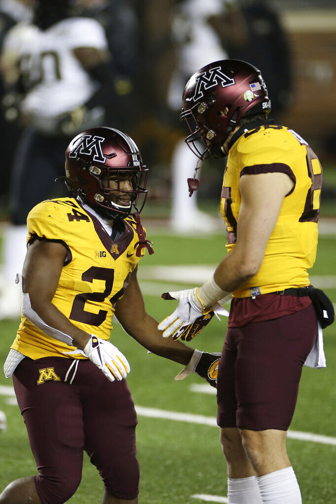 Minnesota running back Mohamed Ibrahim (24) celebrates with tight end Jake Paulson (80) after Ibrahim scored a touchdown against Purdue during the second half of an NCAA college football game Friday, Nov. 20, 2020, in Minneapolis. Minnesota won 34-31. (AP Photo/Stacy Bengs)