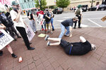 FILE - In this Saturday, May 30, 2020, file photo, a man falls to the ground after an altercation with protesters n Public Square in Wilkes-Barre, Pa. The protest movement over black injustice has also quickly spread deep into predominantly white, small-town America, notably throughout the parts of the country that delivered the presidency for Donald Trump. (Sean McKeag/The Citizens' Voice via AP, File)
