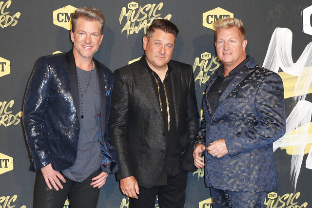 FILE - In this June 6, 2018, file photo, from left, Joe Don Rooney, Jay DeMarcus, and Gary LeVox, of Rascal Flatts, arrive at the CMT Music Awards at the Bridgestone Arena on Wednesday,, in Nashville, Tenn. The country group will bless the broken road this year on their farewell tour on their 20th anniversary together. The group announced Tuesday, Jan. 7, 2020, that they have no future plans for the band after the tour that begins in June and runs through October.(AP Photo/Al Wagner, File)