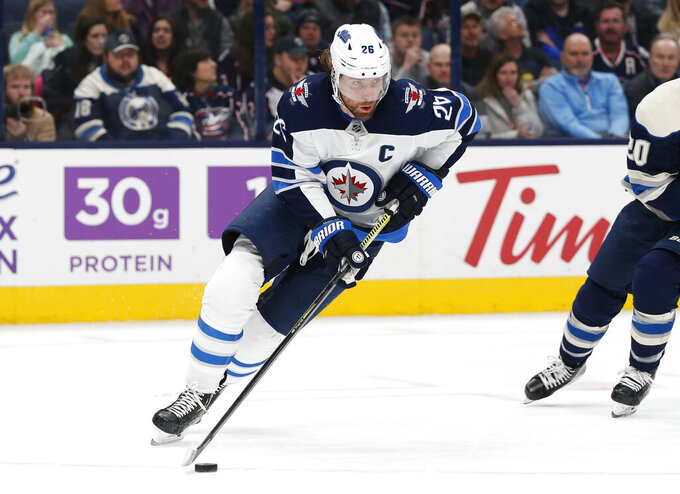 FILE - In this Jan. 22, 2020, file photo, Winnipeg Jets' Blake Wheeler plays against the Columbus Blue Jackets during an NHL hockey game in Columbus, Ohio. Wheeler and the Winnipeg Jets would have been on the road last week, trying to make a final push for the playoffs had the National Hockey League season not been called off because of the pandemic. Now the seven-time All-Star forward is home for dinner each night with his family. (AP Photo/Jay LaPrete, File)