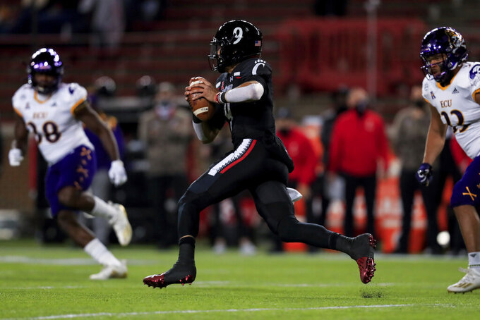 Cincinnati quarterback Desmond Ridder carries the ball during the first half of the team's NCAA college football game against East Carolina, Friday, Nov. 13, 2020, in Cincinnati. (AP Photo/Aaron Doster)