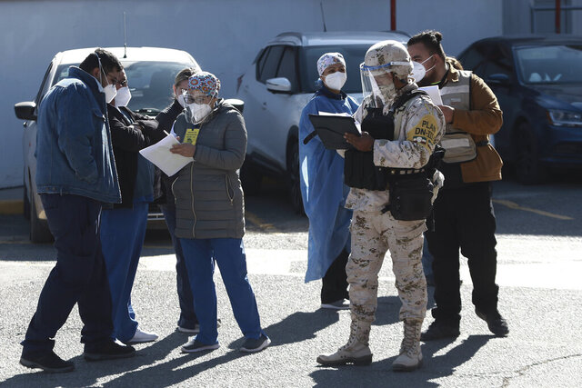 Medical workers are registered to receive the Pfizer COVID-19 vaccine, outside a vaccination center at General Hospital on the first day of coronavirus vaccinations in Ciudad Juarez, Mexico, Wednesday, Jan. 13, 2021. (AP Photo/Christian Chavez)