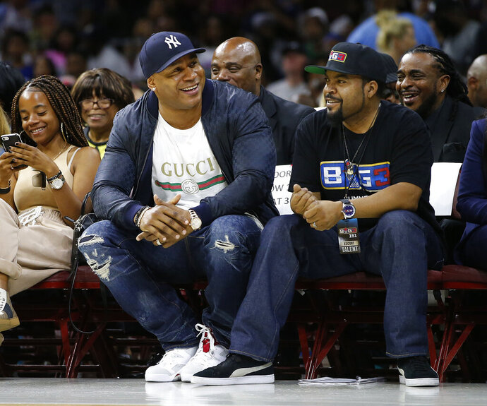 FILE - In this July 16, 2017, file photo, LL Cool J, second from front left, and Ice Cube watch the action as The Power plays the Ghost Ballers during the first half of a BIG3 basketball game in Philadelphia, Pa. Whether sitting courtside in Philly or filming in Hollywood, Ice Cube remains the famous face of his 3-on-3 halfcourt Big3 basketball league. (AP Photo/Rich Schultz, File)