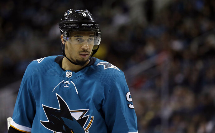 FILE - In this March 20, 2018, file photo, San Jose Sharks' Evander Kane waits for play to resume during the second period of the team's NHL hockey game against the New Jersey Devils in San Jose, Calif. The Sharks are closing in on a seven-year contract with Kane that will keep the high-scoring forward off the free-agent market. A person familiar with the negotiations says the contract is expected to be finalized on Wednesday. The person spoke to The Associated Press on Tuesday night, May 22, on condition of anonymity because the deal hasn't been completed. (AP Photo/Marcio Jose Sanchez, File)