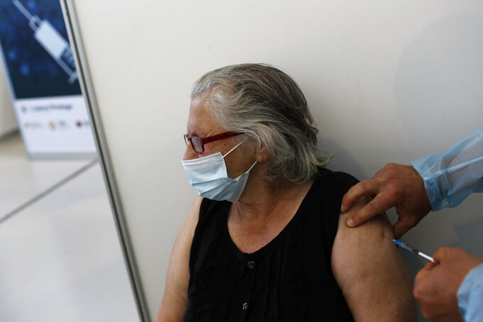 A woman gets a shot of the Johnson & Johnson vaccine at an inoculation center operated by the Portuguese armed forces at Lisbon University's sports stadium, Wednesday, June 23, 2021. The Lisbon region's recent surge in COVID-19 cases is powering ahead, with new infections pushing Portugal's number of daily cases to a four-month high, as a report by health experts found fault with the government's pandemic response. (AP Photo/Armando Franca)