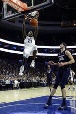 Villanova's Dhamir Cosby-Roundtree (21) hangs form the rim after a dunk past Xavier's Zach Hankins (35) during the first half of an NCAA college basketball game Friday, Jan. 18, 2019, in Philadelphia. (AP Photo/Matt Slocum)
