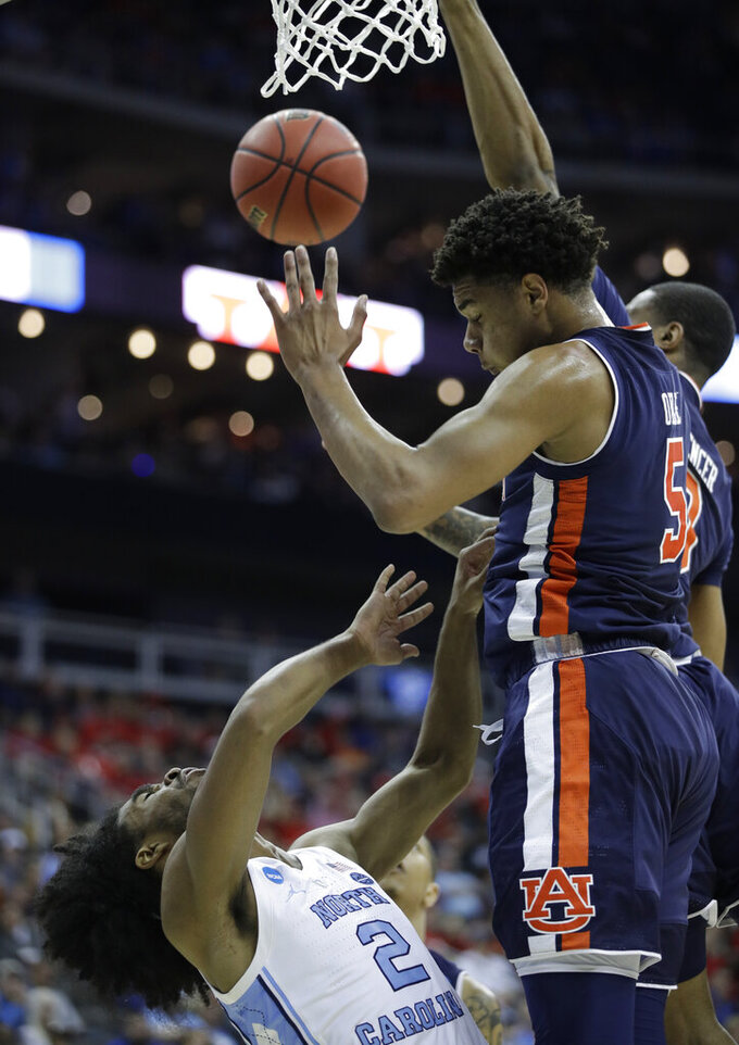 North Carolina's Coby White (2) loses control of the ball on his way to the basket as Auburn's Chuma Okeke, right, defends during the first half of a men's NCAA tournament college basketball Midwest Regional semifinal game Friday, March 29, 2019, in Kansas City, Mo. (AP Photo/Charlie Riedel)