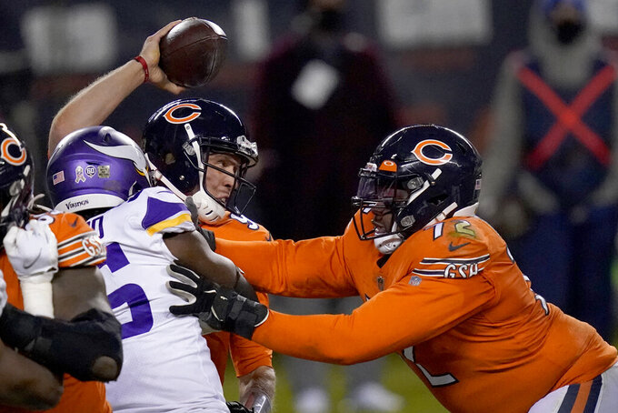 Chicago Bears quarterback Nick Foles tries to throw under pressure from Minnesota Vikings defensive end Ifeadi Odenigbo, left, as Bears offensive tackle Charles Leno Jr., right, pushes Odenigbo during the second half of an NFL football game Monday, Nov. 16, 2020, in Chicago. Foles was injured on the play and left the game. (AP Photo/Charles Rex Arbogast)
