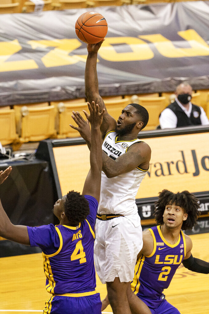 Missouri's Jeremiah Tilmon, top, shoots over LSU's Darius Days, left, and Trendon Watford, right, during the second half of an NCAA college basketball game Saturday, March 6, 2021, in Columbia, Mo. (AP Photo/L.G. Patterson)