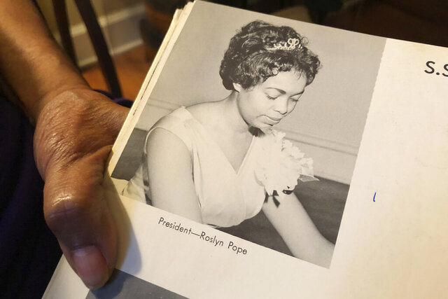 In this March 4, 2020 photo, Roslyn Pope shows her Spelman College yearbook at her home in Atlanta. As a 21-year-old Spelman senior in March 1960, Pope wrote