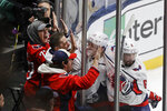 Washington Capitals fans celebrate with Jakub Vrana (13) and Michal Kempny (6) after Vrana scored a goal during the third period of an NHL hockey game against the New York Islanders Saturday, Jan. 18, 2020, in Uniondale, N.Y. The Capitals won 6-4. (AP Photo/Frank Franklin II)