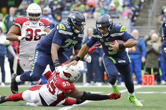 Seattle Seahawks quarterback Russell Wilson (3) is tripped up by Arizona Cardinals linebacker Chandler Jones (55) Seahawks offensive tackle Jamarco Jones (73) looks on during the first half of an NFL football game, Sunday, Dec. 22, 2019, in Seattle. (AP Photo/Lindsey Wasson)