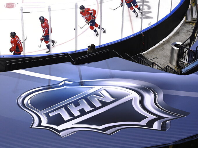 FILE - In this Aug. 14, 2020, file photo, an NHL logo is displayed as Washington Capitals players skate prior to NHL Eastern Conference Stanley Cup playoff hockey game against the New York Islanders in Toronto. The NHL plans to punish unvaccinated players more harshly if they test positive for the coronavirus as part of protocols for the upcoming season. Teams will be able to suspend unvaccinated players without pay if they cannot participate in hockey activities. Those who are fully vaccinated will have any COVID-19 positives treated as hockey injuries and still be paid. (Nathan Denette/The Canadian Press via AP)