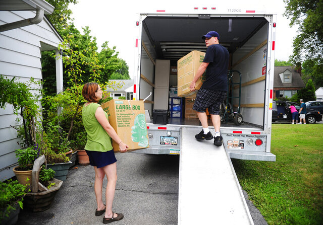 FILE- In this July 13, 2012, file photo, people load a U-Haul truck with boxes while they prepare to move in York, Pa. Many have had to reconsider their living situation because of the pandemic. Before you decide to relocate, make a budget to account for moving costs and the cost of living in your new location. (Chris Dunn/York Daily Record via AP, File)