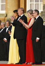 British Prime Minister Theresa May accompanied by her husband Philip, right, stand with U.S. President Donald Trump, and first lady Melania Trump, before a black tie dinner at Blenheim Palace, in Blenheim, England, Thursday, July 12, 2018. (Geoff Pugh/Pool via AP)