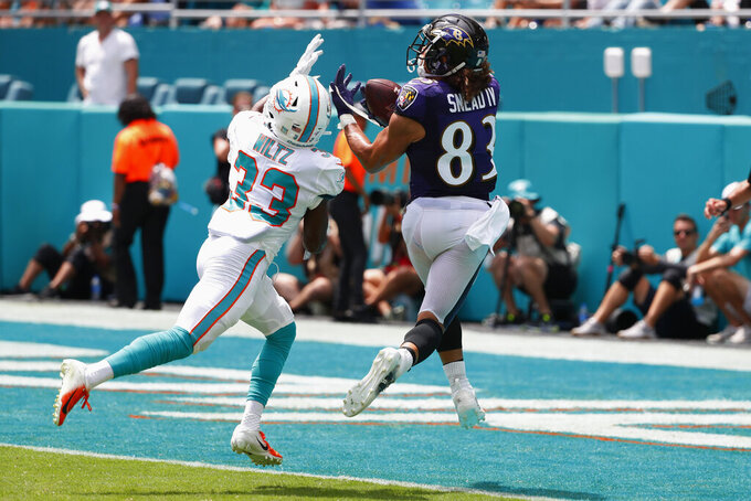 Baltimore Ravens wide receiver Willie Snead (83) catches a pass for a touchdown as Miami Dolphins cornerback Jomal Wiltz (33) attempts to defend, during the first half at an NFL football game, Sunday, Sept. 8, 2019, in Miami Gardens, Fla. (AP Photo/Wilfredo Lee)