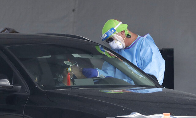 A healthcare worker takes a swab sample from a driver at a drive-through COVID-19 testing site outside Hard Rock Stadium, Wednesday, July 8, 2020, in Miami Gardens, Fla. Florida is one of the nation's hot spots for coronavirus.  (AP Photo/Wilfredo Lee)