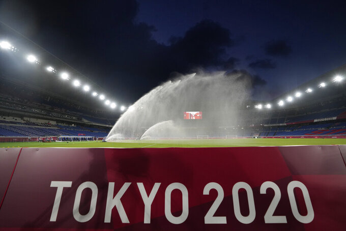 Grounds crew members spray the field down with water before the start of a women's semifinal soccer match between Australia and Sweden at the 2020 Summer Olympics, Monday, Aug. 2, 2021, in Yokohama, Japan. (AP Photo/Kiichiro Sato)