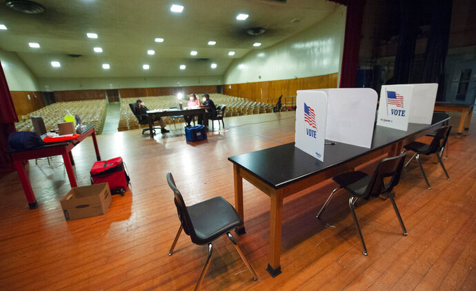 Poll workers try to pass the time during a long morning with no voters up to this point at precinct 38 at Chastain Middle School in Jackson, Miss., Tuesday, June 23, 2020, during the GOP nominee runoff election between Brian Flowers and Thomas Carey for the District 2 Congressional seat. The winner will advance to the November general election to face Democratic U.S. Rep. Bennie Thompson. (Barbara Gauntt/The Clarion-Ledger via AP)