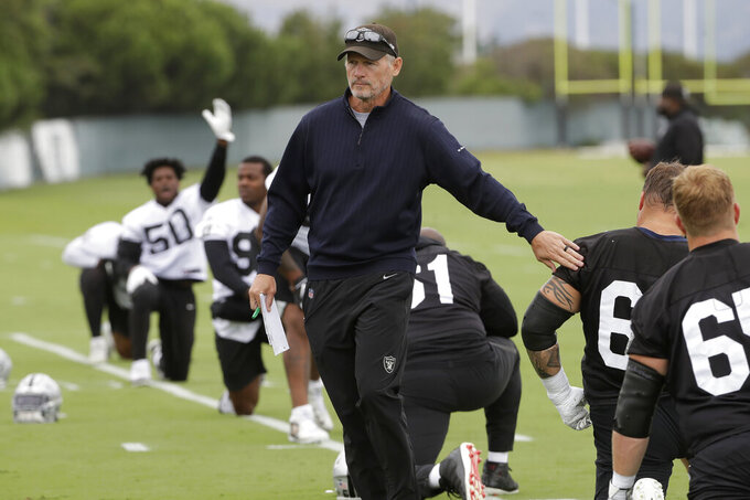 Oakland Raiders general manager Mike Mayock, center, greets Richie Incognito, second from bottom right, during NFL football practice in Alameda, Calif., Tuesday, Aug. 20, 2019. (AP Photo/Jeff Chiu)
