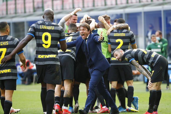 """FILE - In this Sunday, April 25, 2021 file photo, Inter Milan's head coach Antonio Conte and players celebrate after Matteo Darmian scored during the Serie A soccer match between Inter Milan and Hellas Verona, at the San Siro stadium in Milan, Italy. Inter Milan coach Antonio Conte left the newly-crowned Serie A champion by """"mutual consent"""" Wednesday, May 26, 2021 just weeks after leading the Nerazzurri to their first league title in more than a decade. Conte was reportedly unhappy about the club's decision to sell players in this coming transfer window because of financial constraints. (AP Photo/Antonio Calanni, File)"""