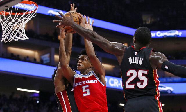 Sacramento Kings guard De'Aaron Fox, center, goes to the basket between Miami Heat's Chris Silva, left, Kendrick Nunn during the second half of an NBA basketball game in Sacramento, Calif., Friday, Feb. 7, 2020. The Kings won 105-97. (AP Photo/Rich Pedroncelli)