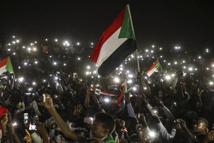 Sudanese protesters use their smartphones' lights during a protest outside the army headquarters in the capital Khartoum on Sunday, April 21, 2019. The organizers of Sudan's protests said Sunday they have suspended talks with the ruling military council because it has failed to meet their demands for an immediate transfer to a civilian government following the overthrow of President Omar al-Bashir.(AP Photo)