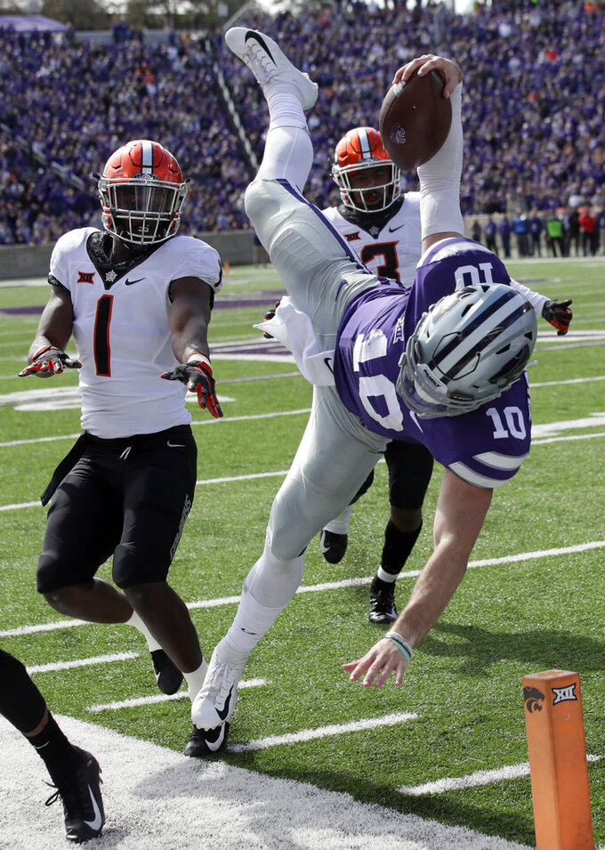 Kansas State quarterback Skylar Thompson (10) is knocked out of bounds by Oklahoma State linebacker Calvin Bundage (1) during the second half of an NCAA college football game in Manhattan, Kan., Saturday, Oct. 13, 2018. Oklahoma State linebacker Kenneth Edison-McGruder (3) follows the play. (AP Photo/Orlin Wagner)