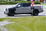 President Joe Biden drives a Ford F-150 Lightning truck at Ford Dearborn Development Center, Tuesday, May 18, 2021, in Dearborn, Mich. (AP Photo/Evan Vucci)