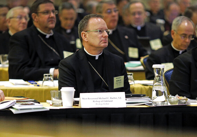 FILE - In this Nov. 12, 2013, file photo, Roman Catholic Diocese of Oakland Bishop Michael Barber, center, listens to a presentation alongside fellow bishops at the United States Conference of Catholic Bishops' annual fall meeting in Baltimore. The Catholic Diocese of Oakland, Calif., has released the names of 45 priests, deacons and religious brothers who officials say are
