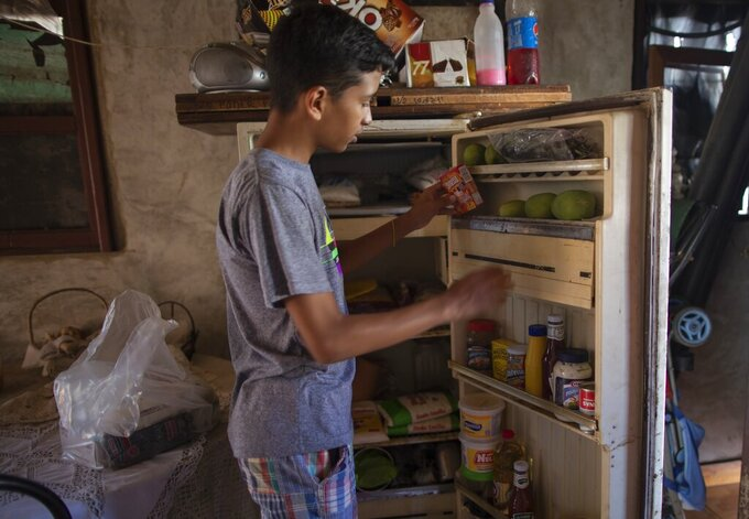 Samuel Andres Mendoza, 14, places his snacks in a rundown fridge at his home in Barquisimeto, Venezuela, Tuesday, March 2, 2021. In a crisis-wracked country where workers earn an average of $2 per month, the sales of Mendoza's drawings can make a big difference for a family budget strained by his need for high-protein foods to deal with a form of malnutrition. (AP Photo/Ariana Cubillos)