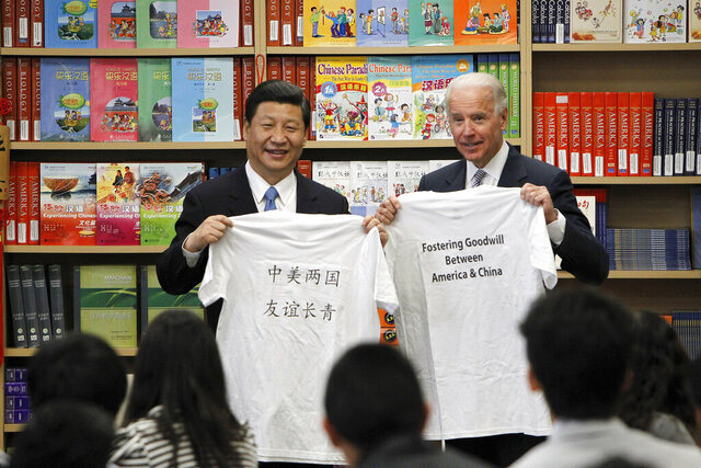 "FILE - In this Friday, Feb. 17, 2012 file photo, Chinese Vice President Xi Jinping and U.S. Vice President Joe Biden hold T-shirts given to them by students during their visit to the International Studies Learning Center in South Gate, Calif. On Friday, May 22, 2020, The Associated Press reported on manipulated photos circulating online altered to show Biden and Xi holding up T-shirts that say ""I (Heart) China."" At the actual event, the Chinese text translates in English to ""China America two countries friendship everlasting,"" while the other reads, ""Fostering goodwill between America & China."