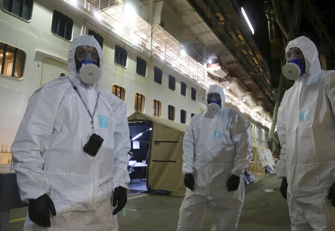 In this Wednesday, April 8, 2020, photo provided by the New South Wales Police, investigators in protective gear prepare to board the Ruby Princess cruise ship at Wollongong, Australia. Police boarded the cruise ship to seize evidence and question crew members after the vessel was linked to hundreds of COVID-19 cases and more than a dozen deaths across Australia. (Nathan Patterson/NSW Police via AP)