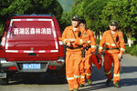 Workers take part in a search for a runaway leopard in Hangzhou in eastern China's Zhejiang province Sunday, May 9, 2021. A search for the last of three leopards that escaped from a safari park in eastern China was ongoing, authorities said Monday, May 10, 2021 as the park came under fire for concealing the breakout for nearly a week. (Chinatopix via AP)