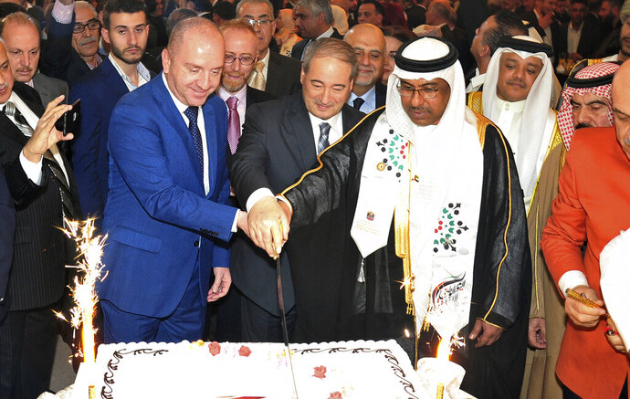 In this Monday, Dec. 2, 2019 photo, released by the Syrian official news agency SANA, the United Arab Emirates Charge d'affaires Abdul-Hakim Naimi, center right, cuts a cake with Syria's Deputy Foreign Minister Faisal Mekdad, center, to mark UAE's National Day, in Damascus, Syria. During the ceremony Naimi praised Syrian President Bashar Assad's