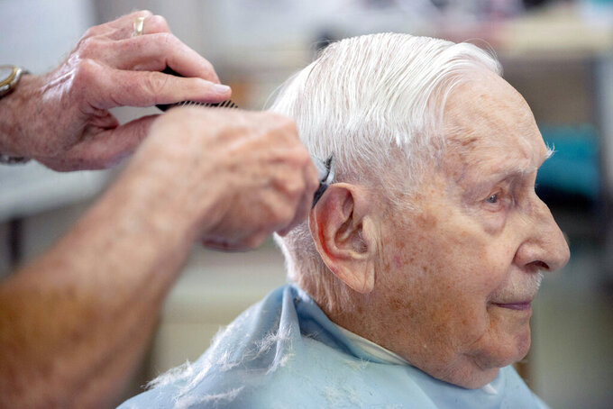 Owosso resident Irwin Smith, 90, gets his hair cut by Karl Manke, Tuesday, May 5, 2020 at Karl Manke's Barber and Beauty Shop in Owosso, Mich. Manke re-opened his doors on Monday in defiance of Gov. Gretchen Whitmer's executive order mandating salons, barbershops and other businesses to stay closed. He has already given nearly 100 haircuts, and fields more calls than that daily, all while continuing to cut hair. (Jake May/The Flint Journal via AP)