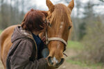 In this Friday, April 5, 2019, photo, Kelly Povroznik kisses her horse Rambling Jack goodbye after having tended to him and her other horse Blackjack at their pasture outside of Clarksburg, W.Va. Povroznik teaches an online college course that has been hampered by slow connections on her computer and phone. There is widespread agreement that expanding broadband internet in rural America is desperately needed. (AP Photo/Craig Hudson)