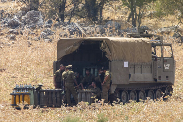 Israeli soldiers gather near shells at an Israeli mobile artillery unit in northern Israel near the border with Lebanon, Tuesday, July 28, 2020. The Israeli military on Monday said it thwarted an infiltration attempt by Hezbollah militants — setting off one of the heaviest exchanges of fire along the volatile Israel-Lebanon frontier since a 2006 war between the bitter enemies. (AP Photo/Ariel Schalit)