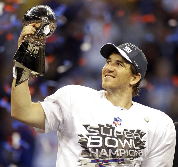 FILE - In this Feb. 5, 2012, file photo, New York Giants quarterback Eli Manning celebrates with the Vince Lombardi Trophy after the Giants' 21-17 win over the New England Patriots in the NFL Super Bowl XLVI football game in Indianapolis. GM Ernie Accorsi got Eli Manning from San Diego in 2004. The deal for the No. 1 overall pick (Manning) saw the Giants send Philip Rivers, the No. 4 overall pick, a 2004 third-rounder, and a first- and fifth-rounder in '05 to the Chargers. (AP Photo/Chris O'Meara, File)