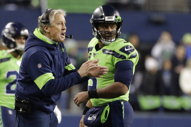 Seattle Seahawks head coach Pete Carroll, left, talks with quarterback Russell Wilson during the first half of an NFL football game against the Minnesota Vikings, Monday, Dec. 2, 2019, in Seattle. (AP Photo/Ted S. Warren)